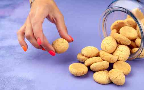 female-hand-takes-cookie-from-scattered-pile-from-transparent-glass-bank (3)@@.jpg